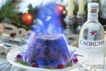 Christmas pudding enveloped in blue flame, bottle of Caorunn gin to the side