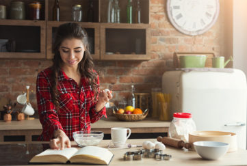 Happy young woman in red check shirt baking pie in loft kitchen at home, using book with recipe