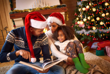 Young parents and girl aged 6 sit by fire and christmas tree reading a storybook together