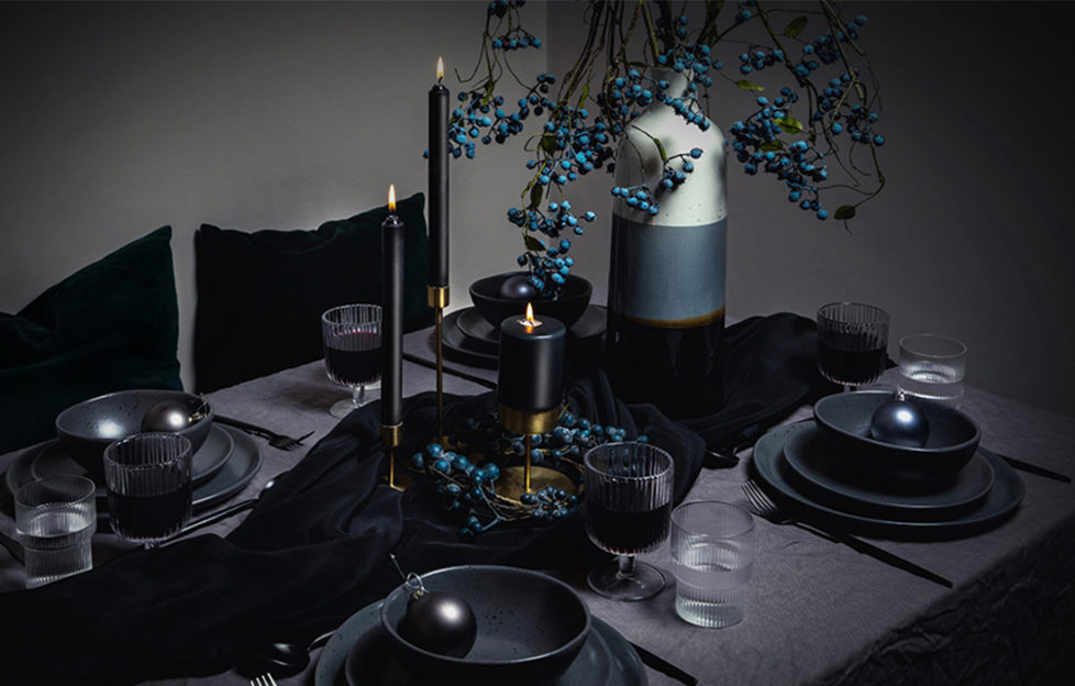 Dark themed Christmas tablescaping with black candles and blue faux berries