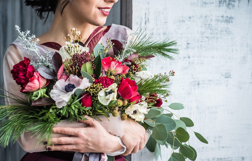 woman with armful of beautiful Christmas flowers in red and white