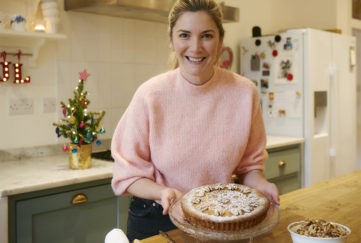 Smiling woman holds cake dusted with icing sugar and decorated with walnuts