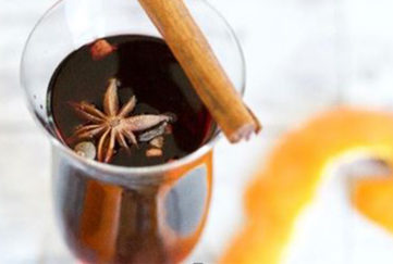 glass of mulled rose wine with cinnamon stick, star anise and orange peel