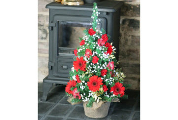 mini floral tree christmas tree on hearth by stove
