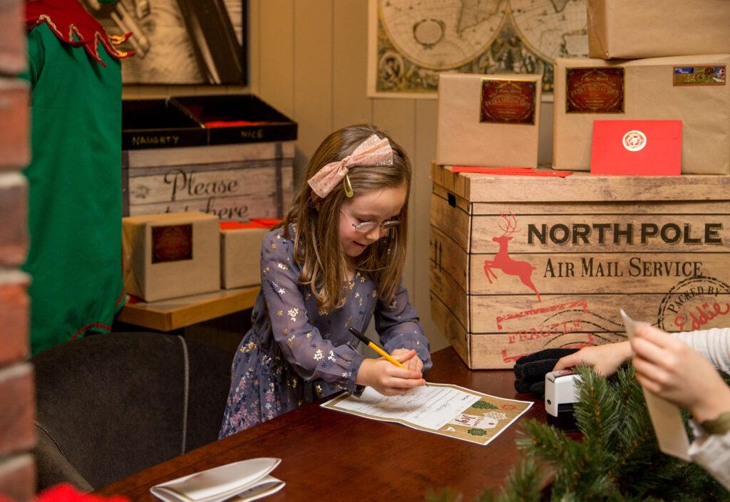 Girl writing letter to Santa at Macdonald Resort, Aviemore
