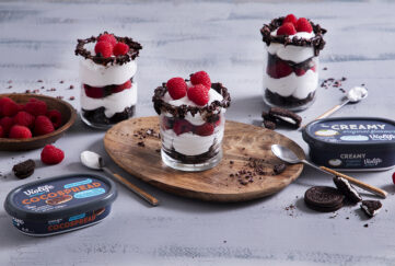 3 glasses of layered cream, chocolate and raspberry desert with tubs of Violife creamy spread and chocolate spread