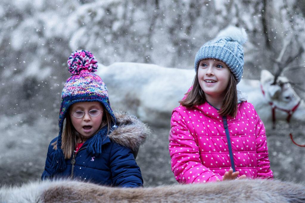 2 girls pet a reindeer at Macdonald Resort, Aviemore