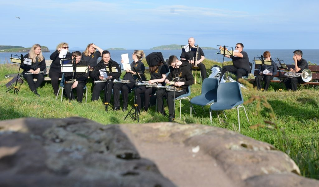 St Columba's footprint with Campbeltown Brass warming up in the background. Amy Paterson centre has taken extreme measures to discourage the midges.