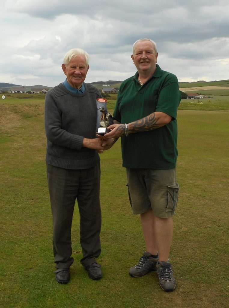 Robert Allan Jr, right, presents Sandy Watson with his trophy and a bottle of Ardmore whisky.