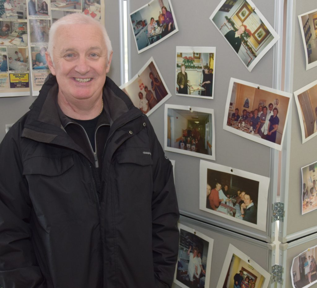 Newly retired John stands beside a photograph of himself on a staff night out 20 years ago.