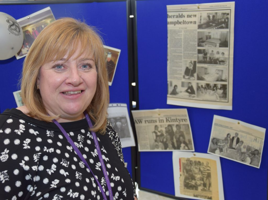 Support services manager Kirsteen Graham stands in front of a Courier cutting which shows her in her first role as a clerical officer in 1993.