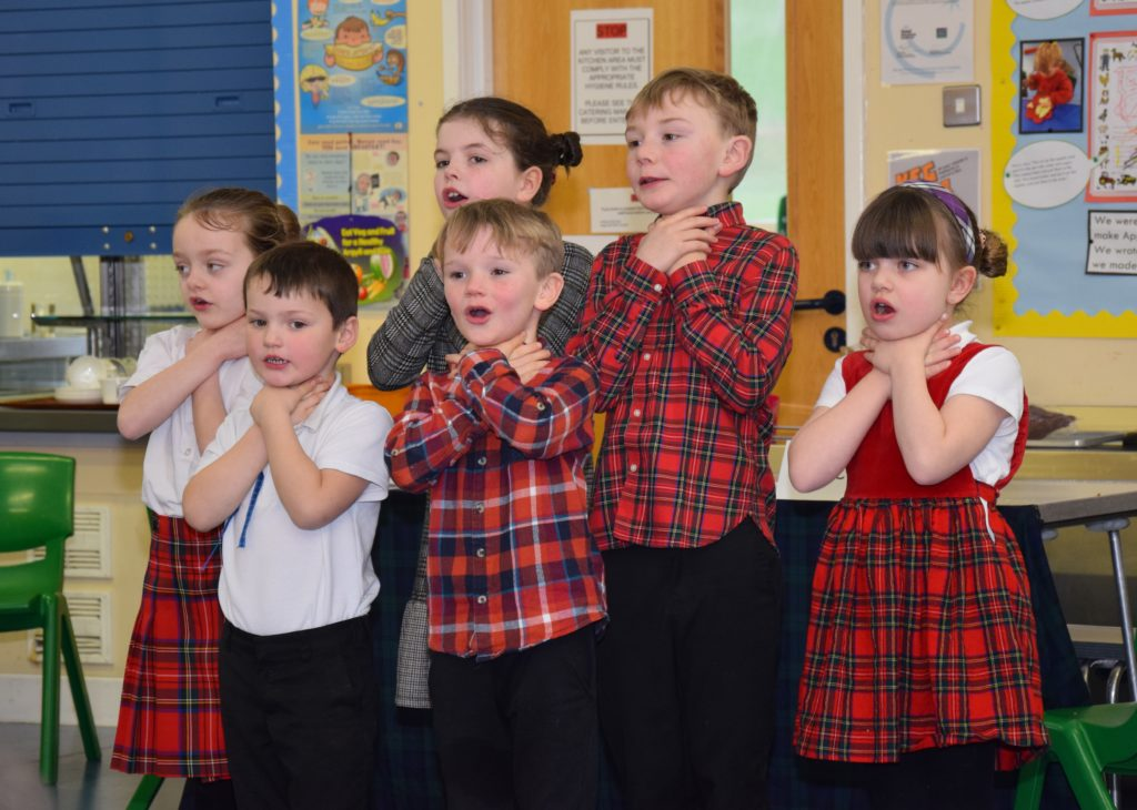 The children 'choking' on hot potatoes while singing 'Tattie soup'.