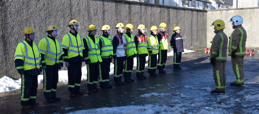 The youngsters stand to attention for fire fighters Iain Hunter and Colin MacColl.