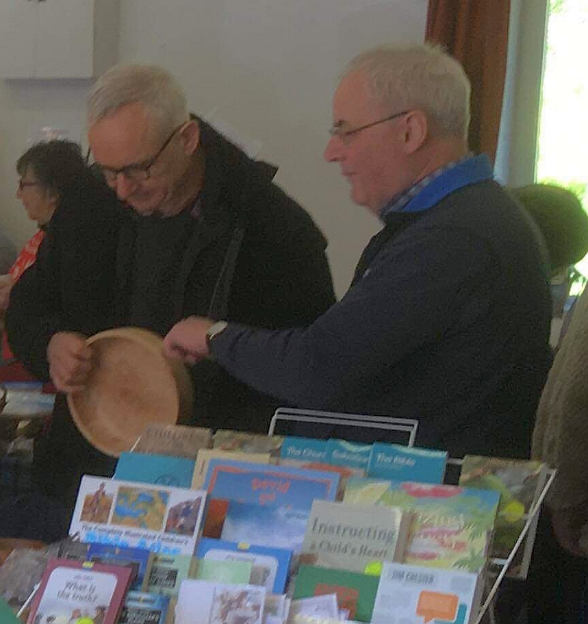 Rodger Crooks shows a potential customer his late father's hand-turned bowls.