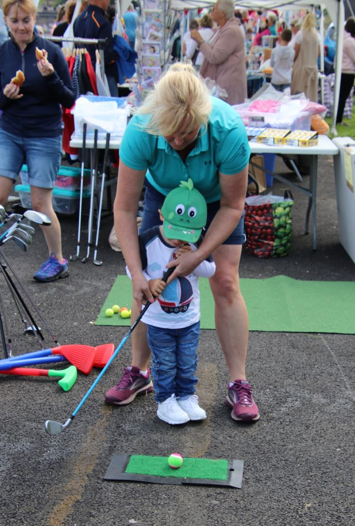 Joanne Campbell helps a younster on Carradale Golf Club's putting stall.