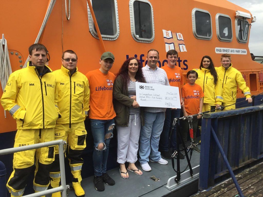 At the cheque presentation, from left: RNLI volunteers Mathew Conley and Paul Ives, left, with Logan, Lynette, Christopher, James and Liam, centre, and RNLI volunteers Carla Jackson and Dhyllon Cox, right.
