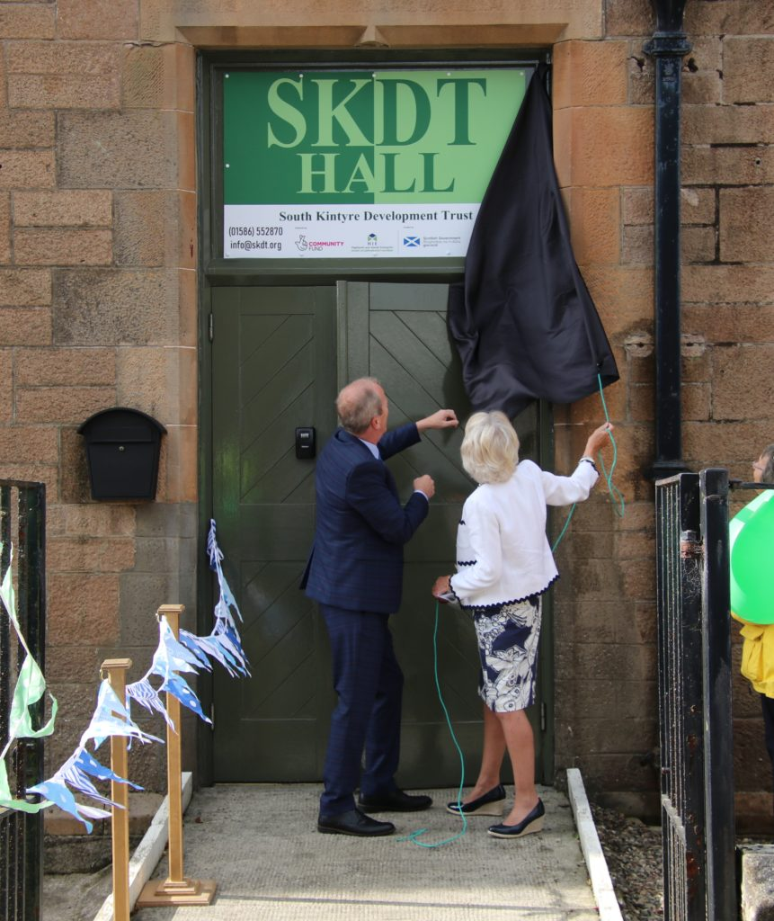 Eric Spence assists Anne Cousin to unveil SKDT Hall's new signage.