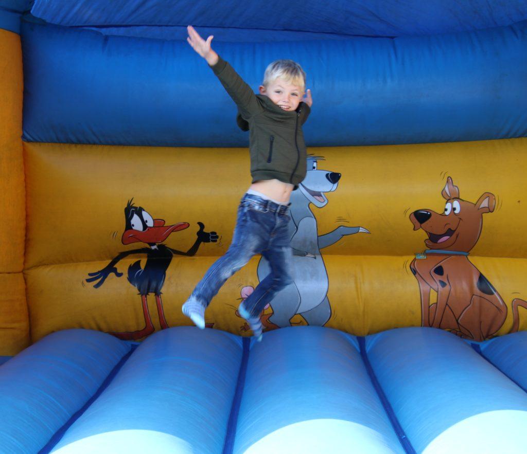 Joshua Sinclair jumps for joy on a bouncy castle.