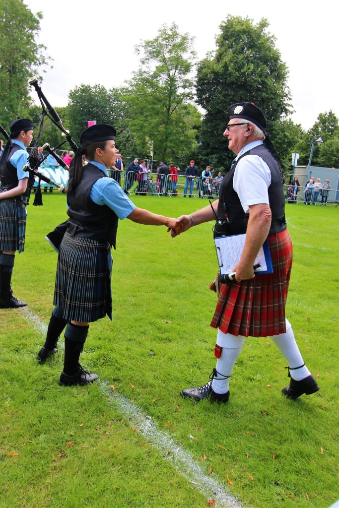 Pipe Major Fiona Mitchell is welcomed to the arena nine by judge.