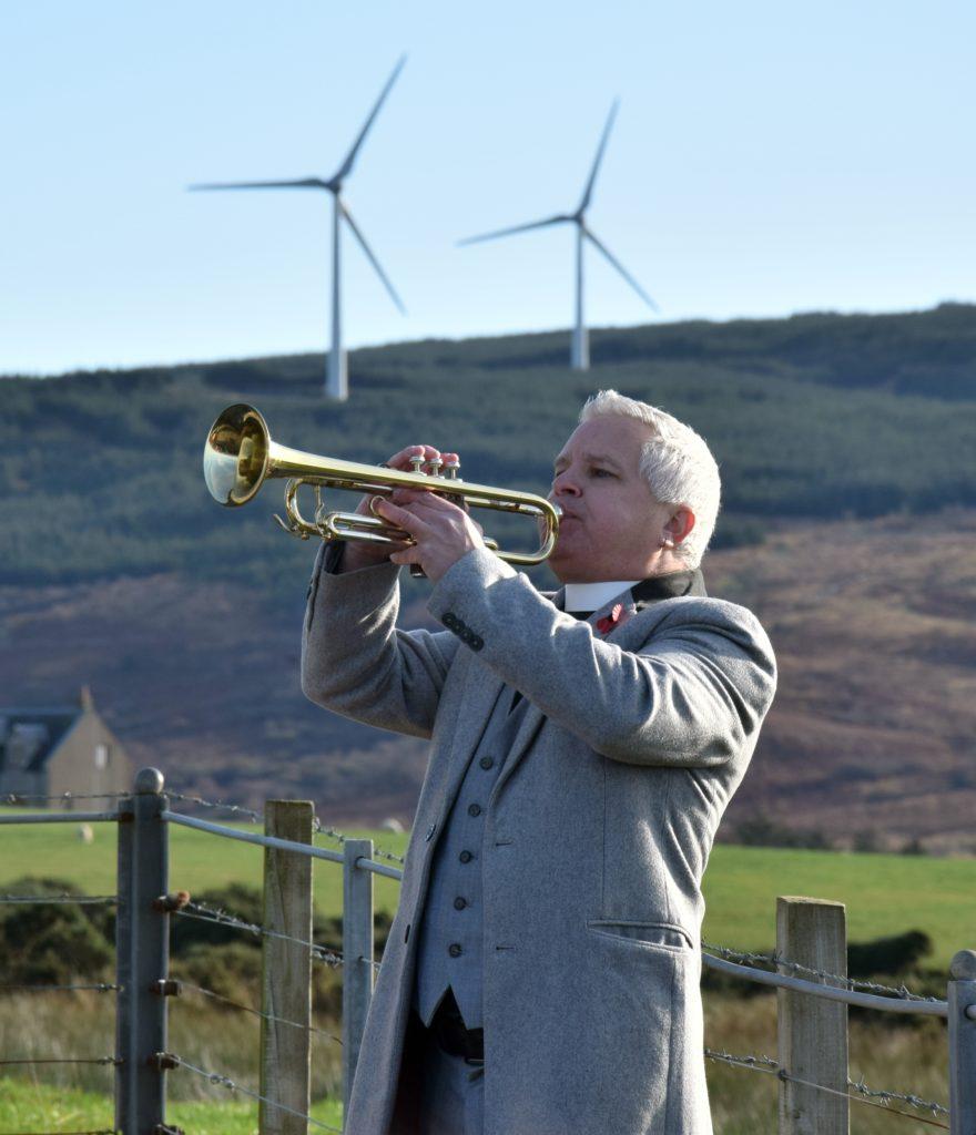 Rev Scott Burton plays The Last Post on his trumpet at Glenbarr War Memorial.