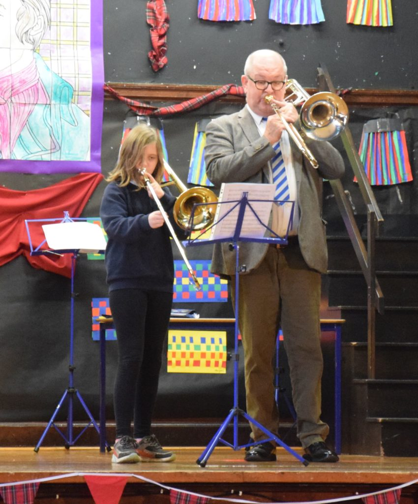 Pupil Eva and brass instructor Mr McDiarmid perform a trombone duet.