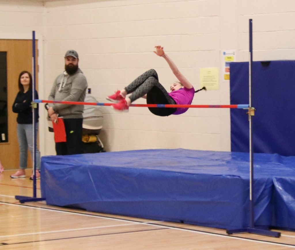 Making it over the bar in the high jump.