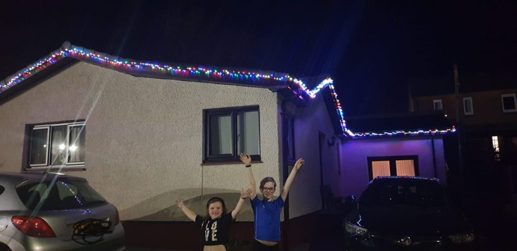 Martine Craig's children Jemma and Gregor with their Christmas lights display.