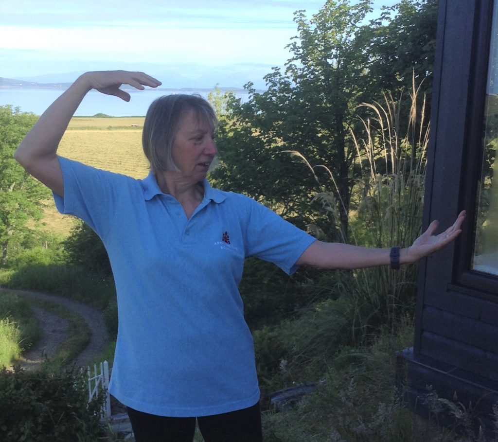 Jackie Fulton performing some Qi Gong in her garden.