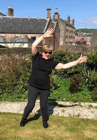 Kate Oman, one of Jackie's Tai Chi students, performing the 'waving hands in the clouds' movement, which is for arthritis, from her home.