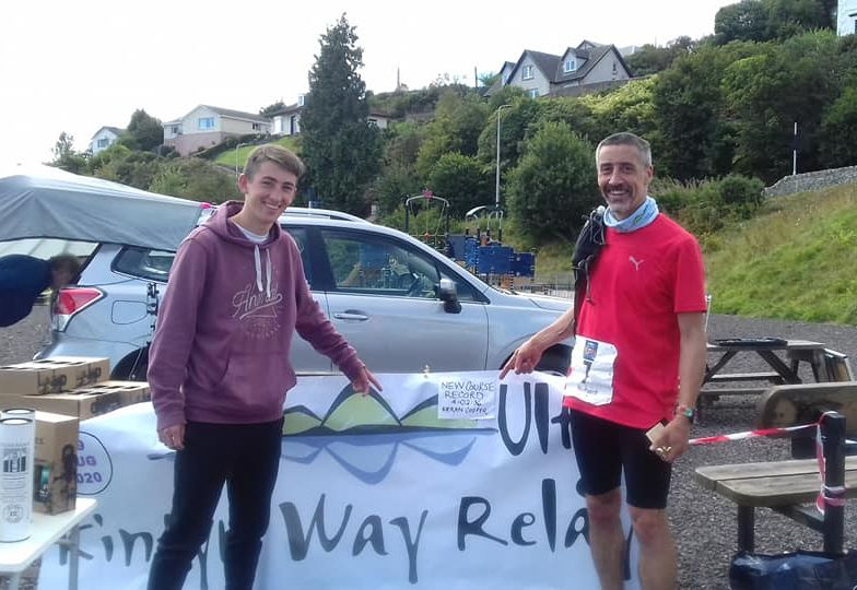 Race winner Kieran Cooper, left, and his father Richard, who finished in tenth place, pointing to the announcement of Kieran's record-breaking run.