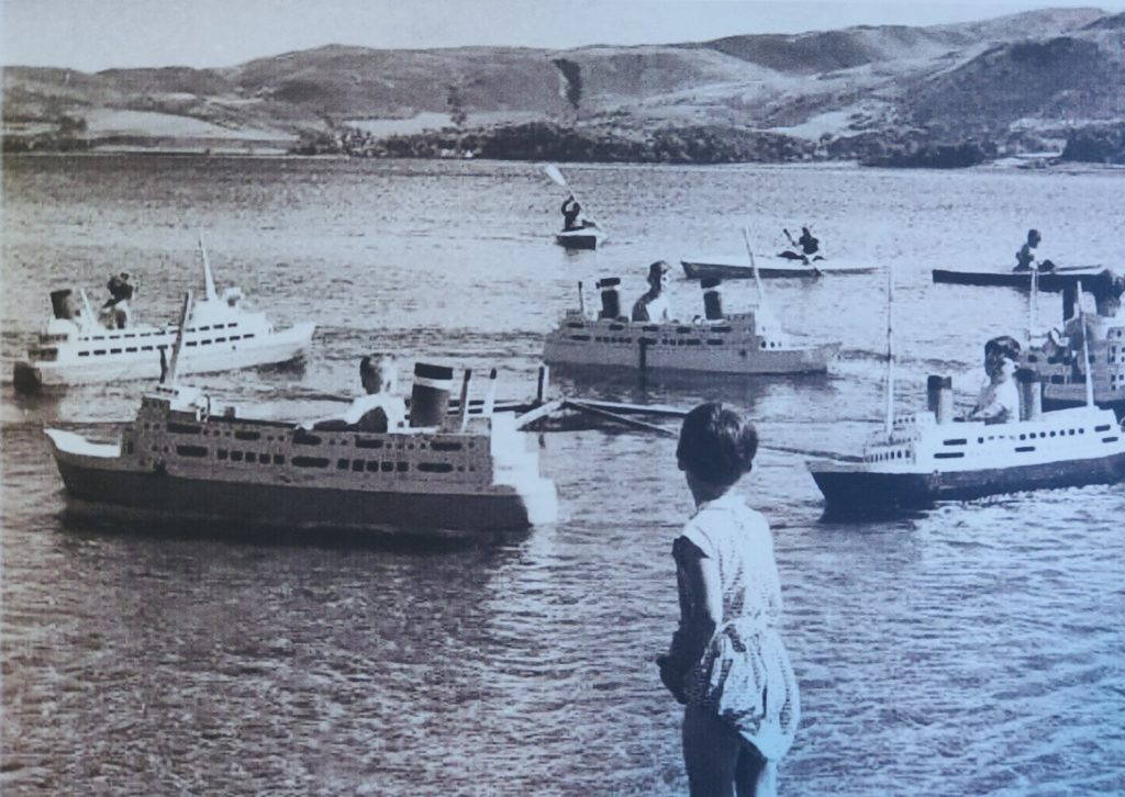 Children in replica steamers made by Mr Shields in the water at Dalintober Beach in the 1960s.