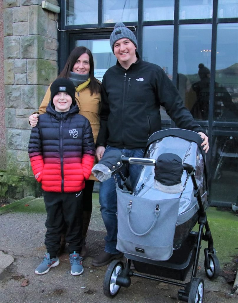Joanne Arbuckle, Lorne McMurchy and Lewis Russell, with little Murray McMurchy tucked up warmly in his pram, waiting to see Santa.