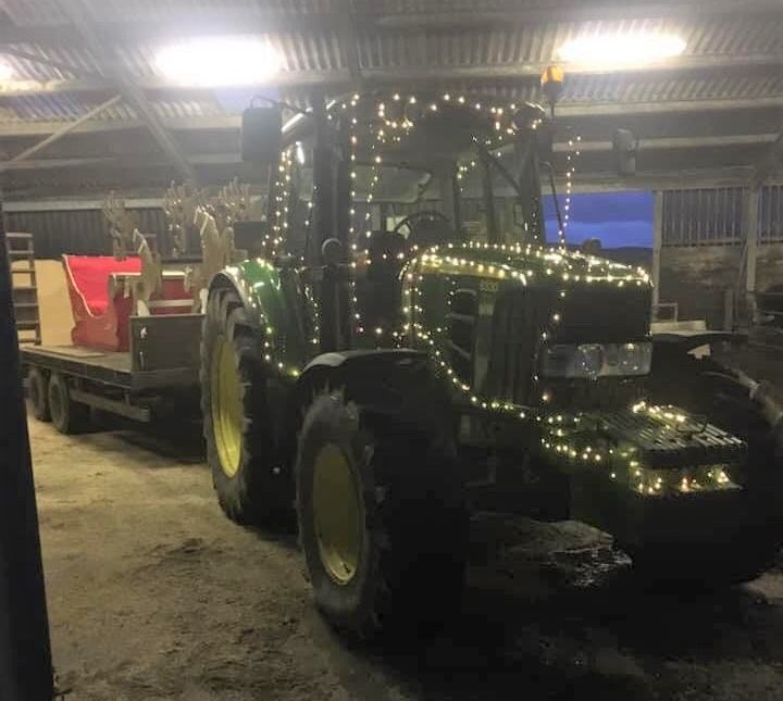 Santa's sleigh was towed by a tractor decorated with fairy lights.