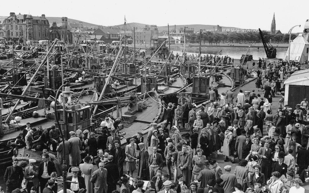 The crowded Old Quay in Campbeltown in the early 1950s, the arrival of one of the regular steamers always being the main event of the day. The large fleet of ring-net fishing boats are tied up in the inner harbour. The Calton 'prefabs' can be seen in the background to the left of the Lochend Church steeple and also in the background to the left of the photograph is The Royal Hotel overlooking Campbeltown Harbour. Photograph: Stenlake Publishing.