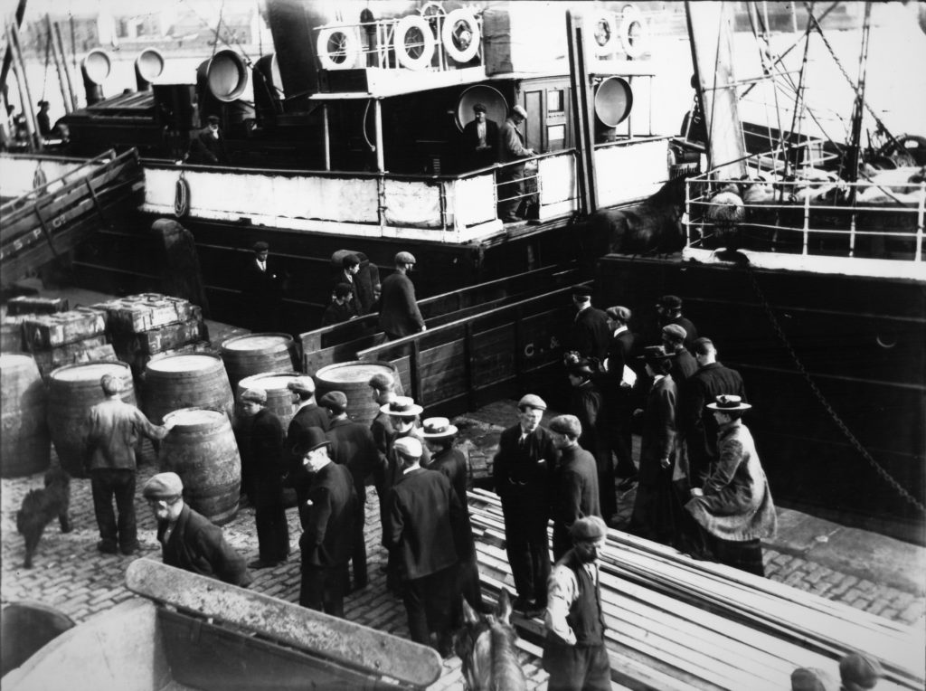 In Campbeltown Harbour, whisky barrels, cargo and passengers await boarding onto a sister ship of the SS Davaar, making this ship either the Kinloch or the Kintyre.
