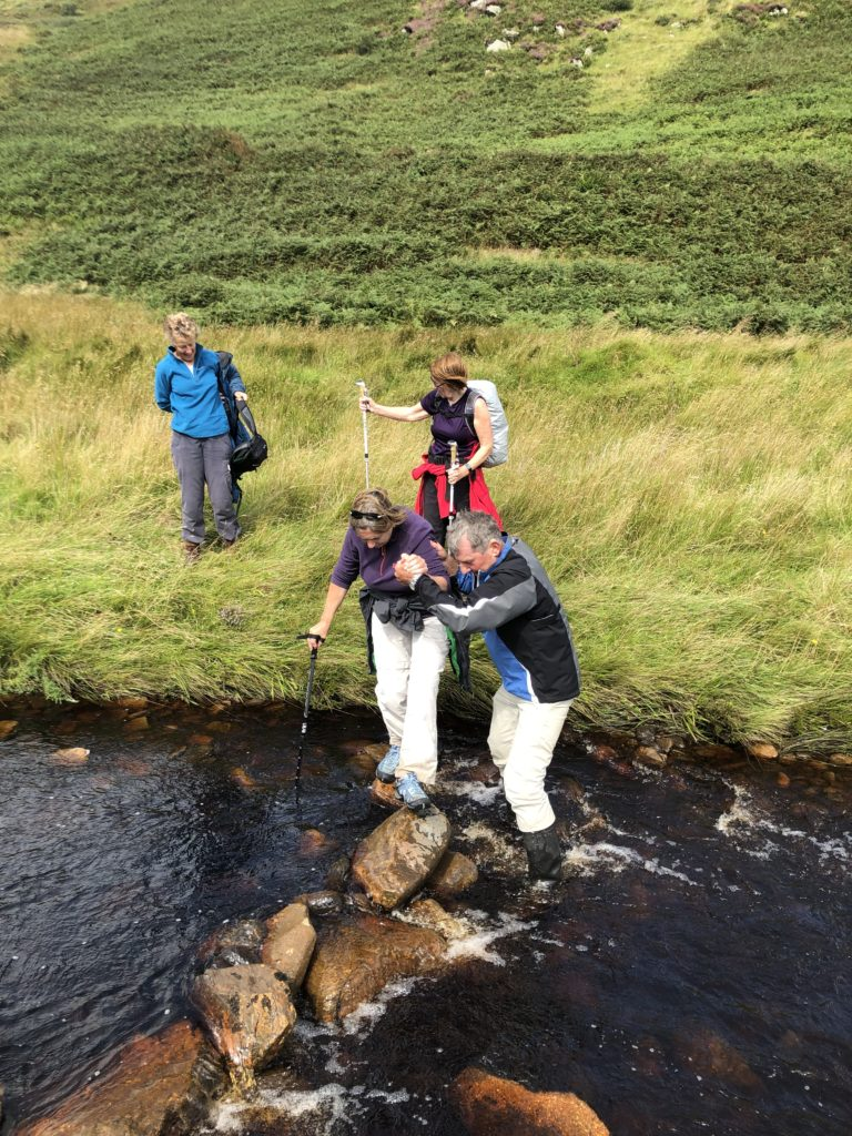 Fun and games crossing a burn during a visit to High Glenadale — Linda Peacock is helped by John Marrison, while Catherine Dobbie and Pat Healey wait to cross.