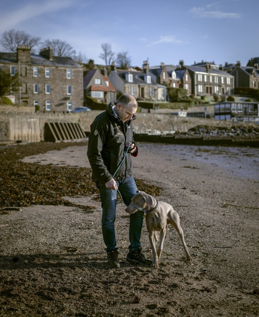 A Hidden Gem: Iain McAlister, distillery manager and master distiller at Glen Scotia Distillery, on Dalintober beach, Campbeltown, in the early morning with his dog, Troy. Photograph: Sophie Gerrard/Document Scotland.