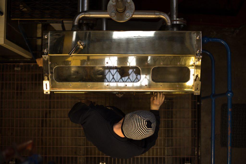 A Handcrafted Process: Gareth Parker, stillman, polishes the spirit safe in the stillroom at Glen Scotia Distillery. Photograph: Jeremy Sutton-Hibbert/Document Scotland.