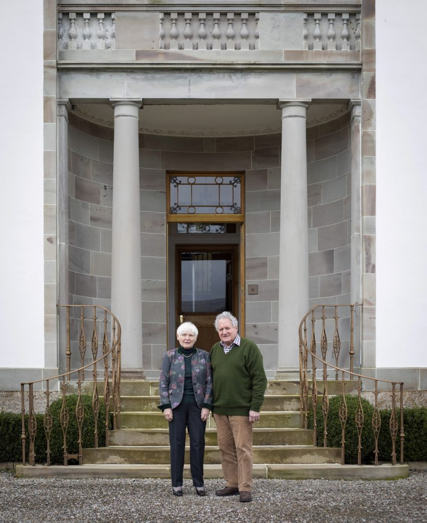 A Whisky Dynasty: David Mayo, a descendant of the Colvill family, one of the 'big three' whisky families at the forefront of Campbeltown's distilling for nearly a century, with his wife Jane at the entrance to their home, Bellgrove, which David inherited. Photograph: Sophie Gerrard/Document Scotland.