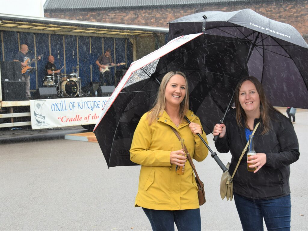 Sisters-in-law Anne Blue and Julie Blue, seen here, braved the elements to watch The Democrats perform at the festival's Up the Close event.