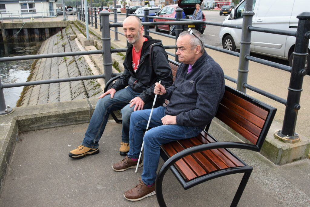 Locals Ian Henry and Eddie Wareham having a seat on one of the recently restored town centre benches.
