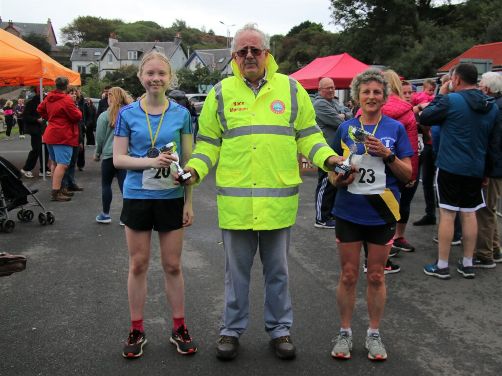 Race organiser Alan Milstead presenting trophies to ladies' 10K winner Susan Turner, right, and runner up Lucy Thomson.
