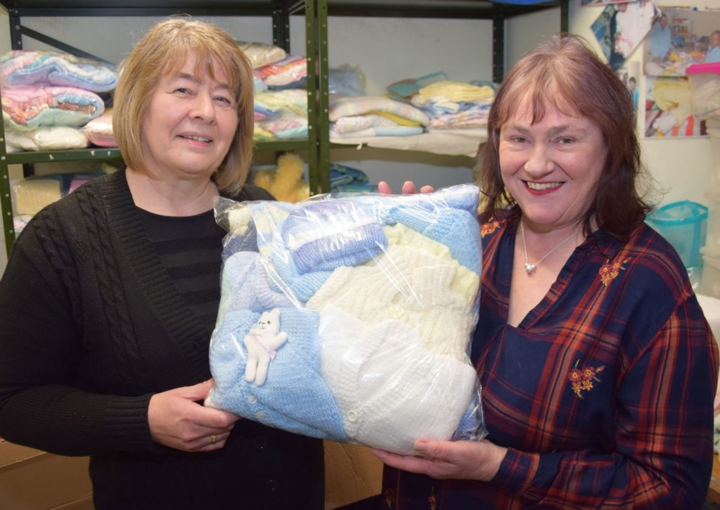 Orion's great-aunt Nannette Campbell, right, receives a second bundle of clothing from Bonnie Babies founder Debby Lamont.