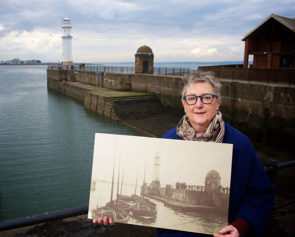 Jane Ryder OBE, photographed at Newhaven Harbour with a print from the 1890s.
