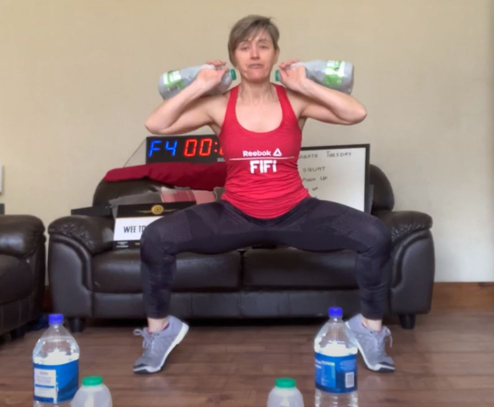 Fiona demonstrates sumo squats with a lift, using make-shift weights.