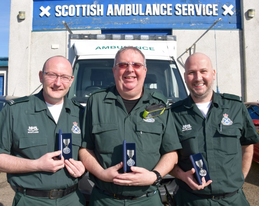 Robert Black, centre, with colleagues and friends Scott Ramsay, left, and James Stevenson, right, after all three received long service medals in 2018.