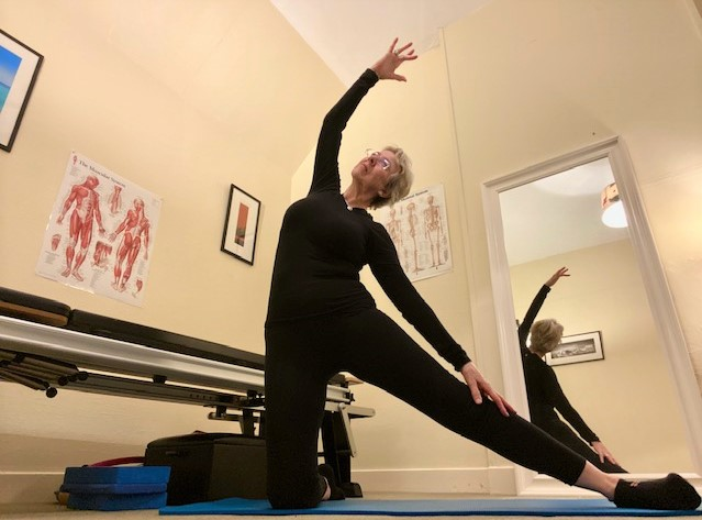 Leone demonstrating spinal side flexion with an inside thigh stretch.