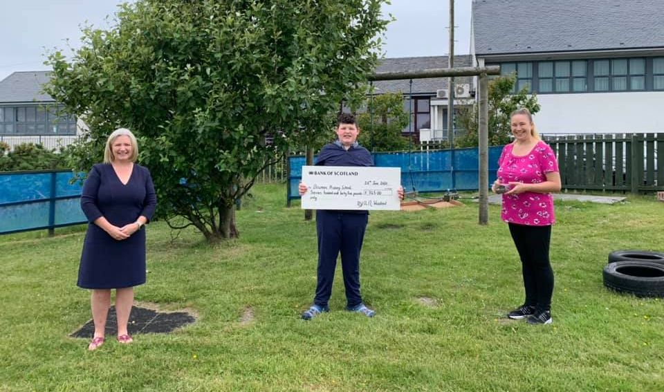 Ryan Woodrow, centre, presenting the cheque to Bowmore Primary School head teacher, Maureen MacDonald, left, and his former class teacher, Linsay MacArthur, right.