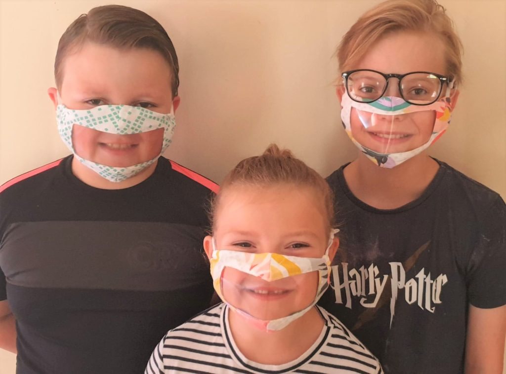 Gregor Craig, right, with his brother Robbie and sister Jemma, sporting their transparent face coverings courtesy of Kintyre Scrubs.