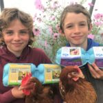 Henny and Charlie Jones holding the egg boxes on which they feature. Henny, left, with two boxes of Kintyre Eggs, and Charlie, right, shows off the new Deliciously Scottish Eggs packaging.
